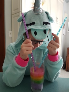 A young girl (my daughter) in a unicorn costume with a rainbow-coloured frozen layered smoothie